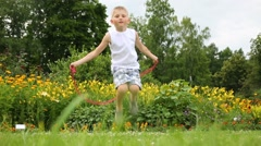 Little boy jumps with skipping rope near flowerbeds Stock Footage
