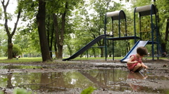 Girl playing in the puddle of mud Stock Footage