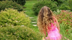 Back of little girl walking at stone path among flowers Stock Footage