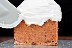 spreading cream on cake with spatula - stock photo