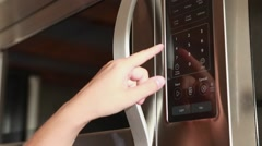 A woman using the timer on the microwave Stock Footage