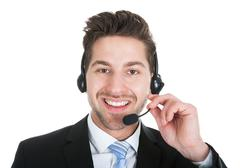 Young male call center representative wearing headset over white background Kuvituskuvat