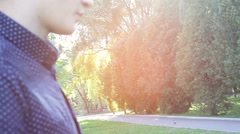Boy is standing in a park in the setting sun Stock Footage