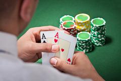 man with ace cards playing poker - stock photo