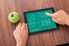 student solving math's problem on digital tablet - stock photo