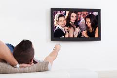 man listening to karaoke on tv - stock photo