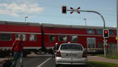 Cars waiting at a railroad crossing and some people passing away Stock Footage