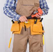 repairman holding adjustable wrench - stock photo