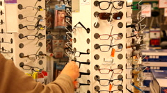 Stock Video Footage of Selecting cheap reading glasses from the supermarket