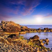 sea wave breaks about boulders at sunset - stock photo