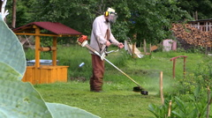 Gardener cut grass near rural well house and plant leaves Stock Footage