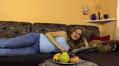 Woman lie on couch, palm belly, press button remote control tv. Stock Footage