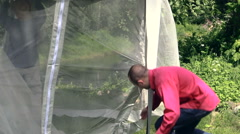 Man bind to arbor bar mosquito screen on windy day, tilt down. Stock Footage