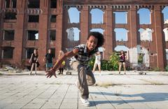 energetic street dancer lunging at the camera - stock photo