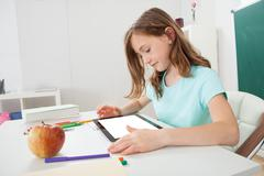 cute schoolgirl using digital tablet at table in study room - stock photo