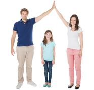 Full length portrait of parents forming house roof shape above daughter over  Stock Photos