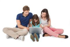 Portrait of happy family sitting with laptop over white background Stock Photos