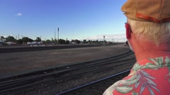 train depot, man watching train at distance. - stock footage