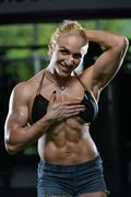 muscular woman showing abs - stock photo