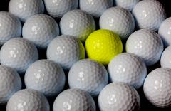 Stock Photo of golf balls. single yellow ball mixed within many white balls.