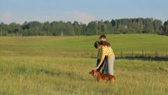 Two friends spending time with dog in the field, childhood, static Stock Footage