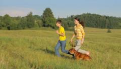 Two friends spending time with dog in the field, childhood Stock Footage