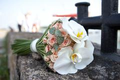 Bouquet of fresh flowers near the bollard. Wedding bouquet of roses and orchids. Stock Photos