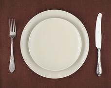 Table setting. Beige plates and vintage fork and knife on a brown linen tableclo Stock Photos