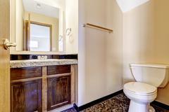 old wooden bathroom vanity cabinet with granite top - stock photo