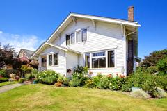 simple house exterior with green front yard - stock photo