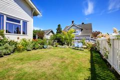 backyard with sitting area and flower beds - stock photo