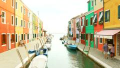 VENICE, ITALY - CIRCA 2014: Colorful houses of Burano as elderly couple passes. Stock Footage