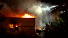 Fireman ventilating building on fire with pike pole Stock Footage