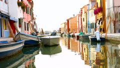 VENICE, ITALY - CIRCA 2014: Burano canal and boats as people pass. Stock Footage