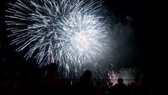 People in silhouette watching and applauding grand finale at fireworks display Stock Footage