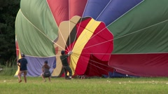 Hot-air ballon workers pulling on cords at balloon landing - stock footage