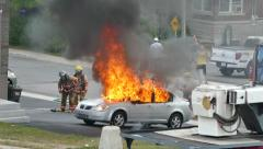Firemen arriving on scene of car fire fully involved in flames Stock Footage