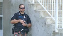 Police officer with gun in hands hiding behin outdoor stairways Stock Footage