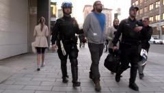 Riot police walking with a protester in handcuffs Stock Footage