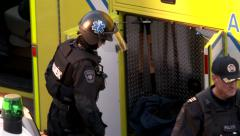 Tactical paramedic stowing gear in ambulance - stock footage