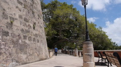 Man walking along  Paseo de la Princesa baywalk - Old San Juan Stock Footage