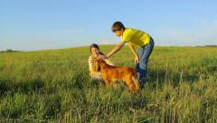 Two young friends and dog spending time together in the field in summer Stock Footage