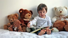 Boy, reading a book, educating, teddy bears around him Stock Footage