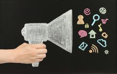 Hand holds chalk megaphone with flying icons Stock Photos