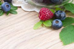 Stock Photo of fresh raspberry anf blueberries with green leaves as frame  on wooden table