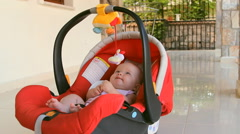 An infant child in the avtolyulka, carrycot, playing, talking Stock Footage