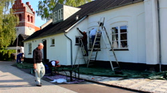 Men working together on painting a building Stock Footage