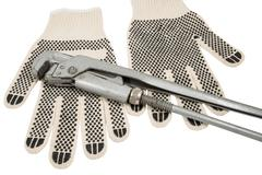Dirty leather gloves and monkey wrench Stock Photos