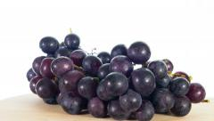 Black grapes rotates, white background, 4k stop motion Stock Footage