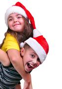 Happy children with santa claus red hats Stock Photos